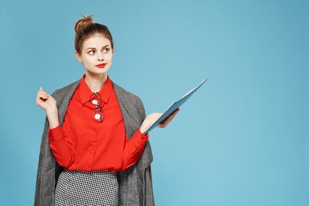 手作業の青い背景で彼女の肩のフォルダーにジャケットを着たビジネス女性。高品質の写真