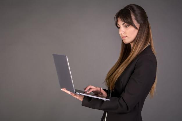 Деловая женщина с ноутбуком на сером фоне