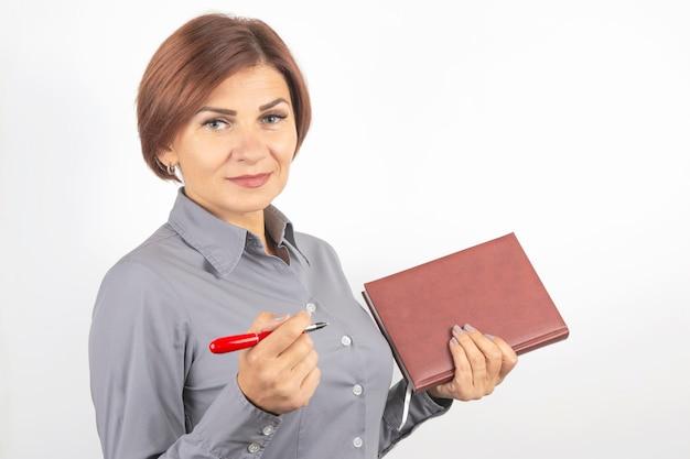 手に赤いペンとノートを持つビジネス女性