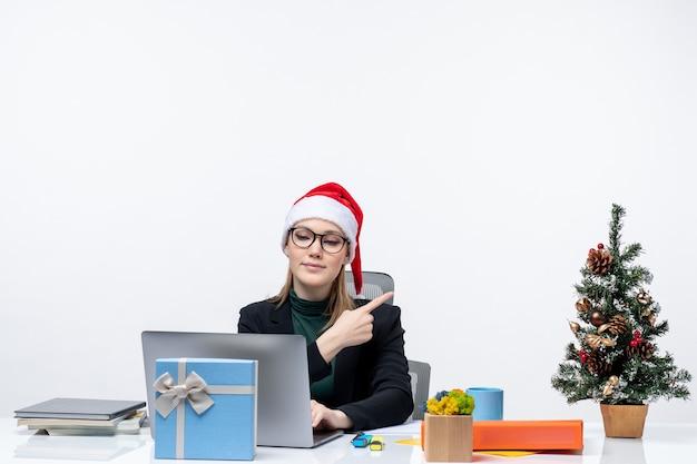 Деловая женщина в шляпе санта-клауса сидит за столом с елкой и подарком