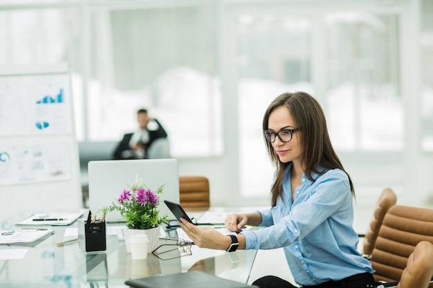 현대 사무실에서 직장에서 스마트 폰으로 비즈니스 여자.