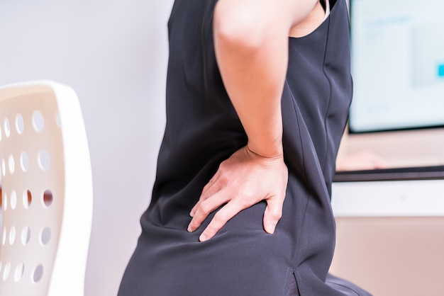 Business woman with back pain an office. healthcare and medical concept