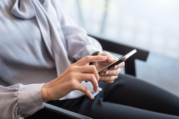 Деловая женщина с перерывом и с помощью любимого смартфона в офисе.