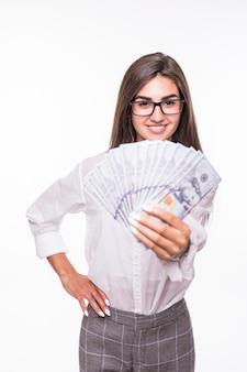 La donna di affari con capelli castani in abbigliamento casual tiene molte banconote del dollaro sopra bianco