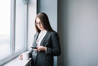 Деловая женщина с кофе с помощью смартфона в окне
