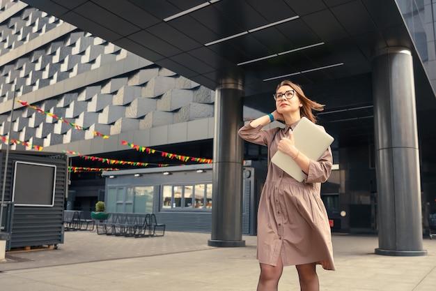 현대 기업 건물의 배경에 컴퓨터와 비즈니스 여자.