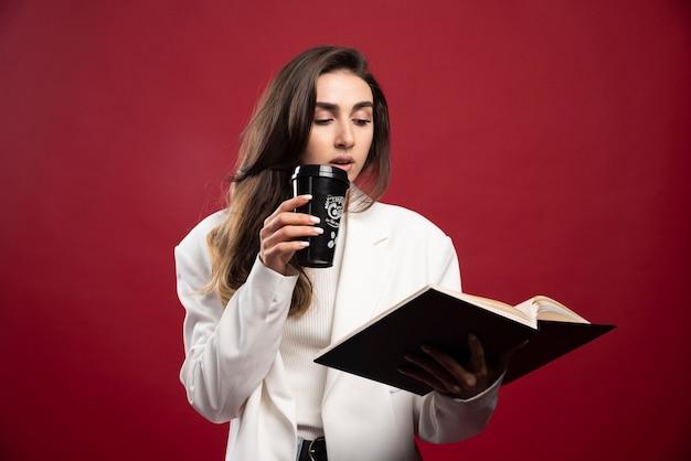 Donna d'affari con una tazza alla ricerca su un taccuino