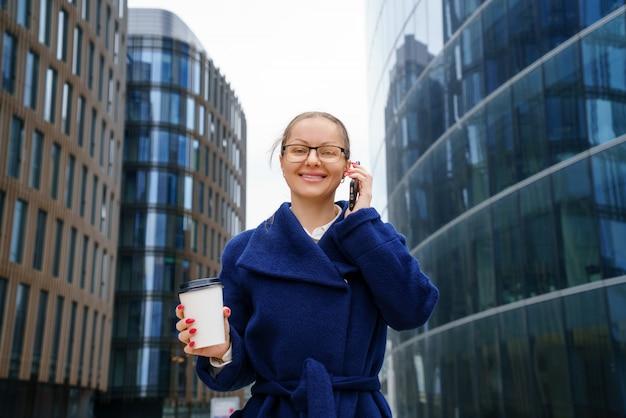 Деловая женщина с чашкой кофе в руке разговаривает по телефону за пределами офисного здания. концептуальная горизонтальная фотография. низкий угол выстрела