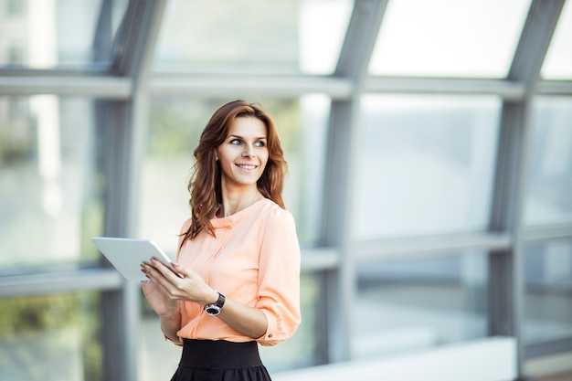 Business woman with digital tablet standing near a large window in a modern office