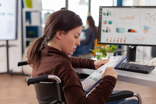 締め切りプロジェクトのために働いている障害を持つビジネスウーマンは、営業所の車椅子に座っているクリップボードチェックグラフからドキュメントを読んでいます
