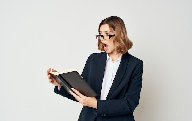 軽い肖像画のスーツの金融に関する文書を持つビジネスウーマン