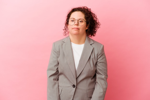 ピンクの背景に分離されたダウン症のビジネス女性は肩をすくめると混乱した目を開いています。
