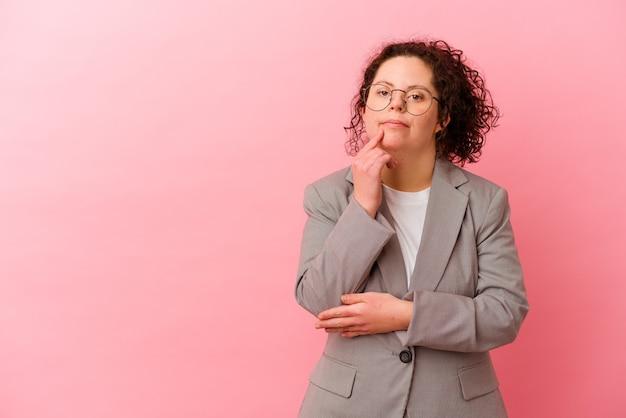 핑크 벽에 고립 된 다운 증후군 비즈니스 여자 복사 공간을보고 뭔가에 대해 생각을 편안 하 게합니다.