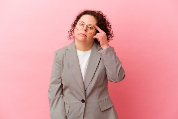 집게 손가락으로 실망 제스처를 보여주는 분홍색 벽에 고립 된 다운 증후군을 가진 비즈니스 우먼