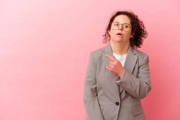 Business woman with down syndrome isolated on pink background pointing to the side