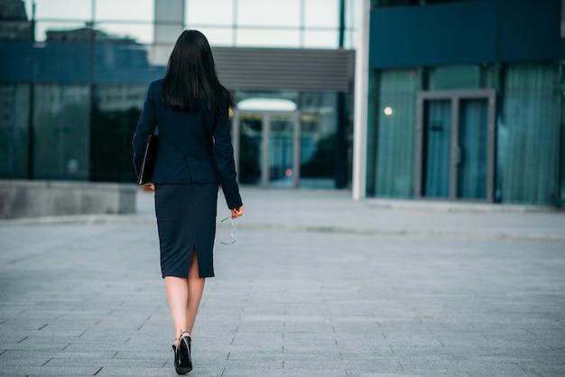 手に眼鏡とラップトップ、背面図を持つビジネス女性。近代的な建物、金融センター、街並み。