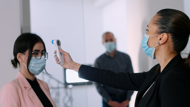 Business woman with face mask checking collegues forehead temperature using infrared thermometer to avoid virus infection. team respecting social distance while working in company office
