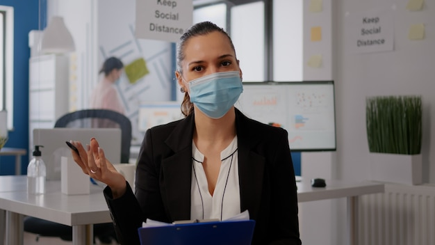 원격 팀과 온라인 웹 인터넷 화상 통화 중에 얼굴 마스크를 쓴 비즈니스 여성. 전염병 동안 화상 통화 회의 확대 회의에서 새로운 일반 사무실에서 커뮤니케이션 회의를 하는 프리랜서