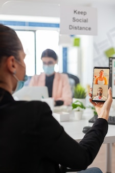 스마트폰으로 화상 회의를 하는 동안 안면 마스크를 쓴 비즈니스 여성, 글로벌 전염병 동안 코로나바이러스 독감 예방으로 사회적 거리를 유지합니다. 인터넷 웹 화상 통화 채팅 메시지 사용