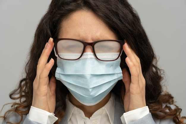 Business woman with foggy glasses from breath caused by wearing disposable mask on grey background