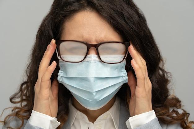회색 배경에 일회용 마스크를 착용하여 호흡에서 안개가 자욱한 안경을 가진 비즈니스 우먼