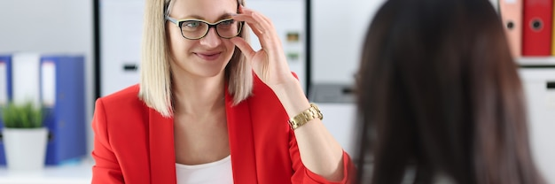 Business woman with glasses communicating with colleague at table
