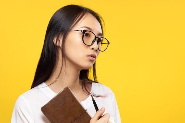 マネージャーのオフィスの黄色の手にメガネのメモ帳を持つビジネス女性。