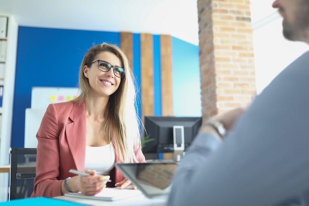 안경을 쓰고 테이블에 앉아 남자와 인터뷰를 하는 비즈니스 우먼. 고용 개념