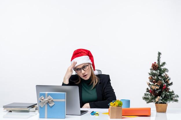 Donna d'affari con il suo cappello di babbo natale seduto a un tavolo con un albero di natale e un regalo