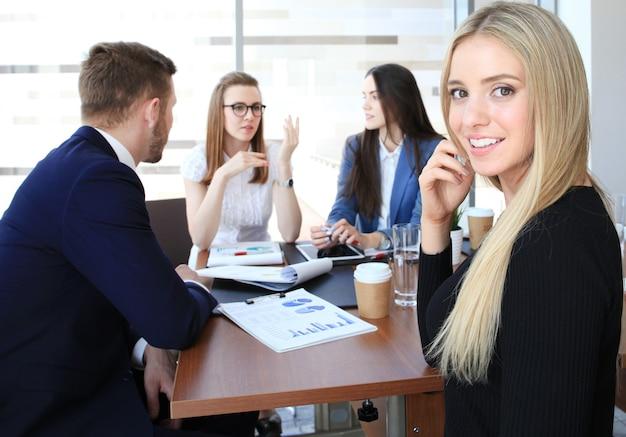 Деловая женщина с ее персоналом, группа людей в фоновом режиме в современном ярком офисе в помещении.