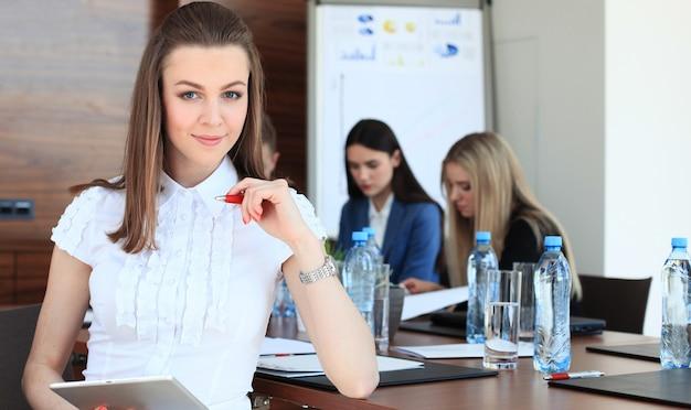 직원이 있는 비즈니스 여성, 현대적인 밝은 사무실 실내에서 배경에 있는 사람들.