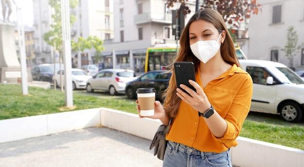 街の通りで立ってスマートフォンアプリを使用してkn95ffp2フェイスマスクを持つビジネスウーマン