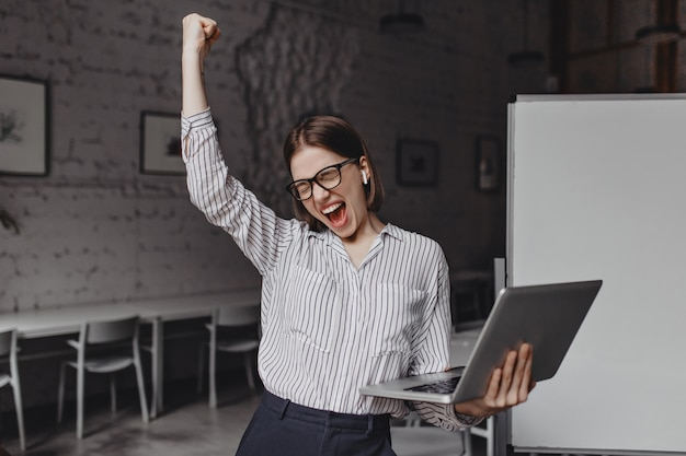Business woman with laptop in hand is happy with success. portrait of woman in glasses and striped blouse enthusiastically screaming and making winning gesture.