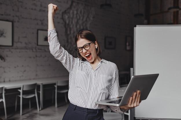 손에 노트북 비즈니스 여자는 성공에 만족합니다. 열정적으로 비명과 승리 제스처를 만드는 안경과 스트라이프 블라우스에 여자의 초상화.