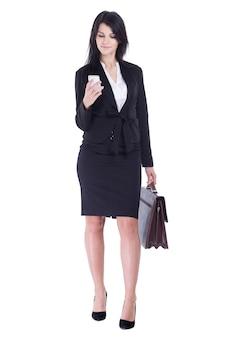 가죽 서류 가방을 가진 비즈니스 우먼은 흰색 배경에 그녀의 스마트폰 .isolated에서 sms를 읽습니다.