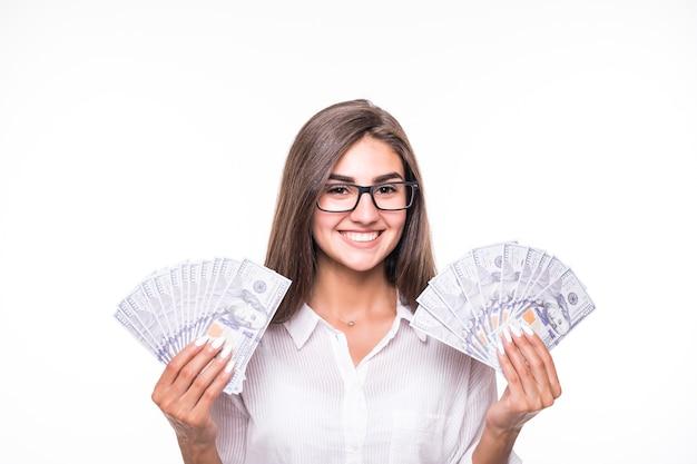 La donna di affari con i capelli marroni lunghi in vestiti casuali tiene molte banconote sopra bianco
