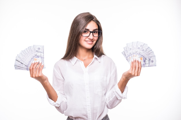 Business woman with long brown hair in white clothes hold lots of dollar banknotes over white