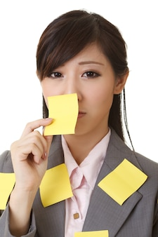 Business woman with many yellow memo note on her body, closeup portrait.