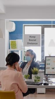 彼女の同僚が働いている間、パートナーとスマートフォンで話している医療用フェイスマスクを持つビジネスウーマン...
