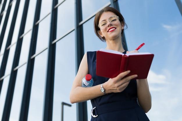 ビジネスの女性とメモ帳で、モダンな高層ビル