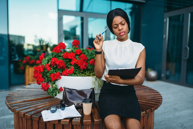 Деловая женщина с блокнотом, отдыхая на скамейке во время перерыва перед офисным зданием.