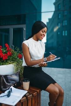 Деловая женщина с блокнотом сидит на скамейке во время перерыва перед офисным зданием