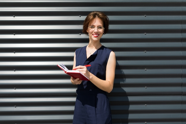 Business woman with notepad on a wall