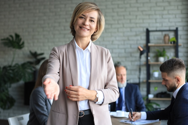Business woman with an open hand ready for handshake in office.
