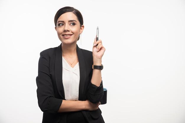 白い背景にスーツを着てポーズをとる鉛筆を持つビジネスウーマン。高品質の写真