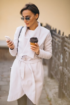 Business woman with phone drinking coffee outside in street