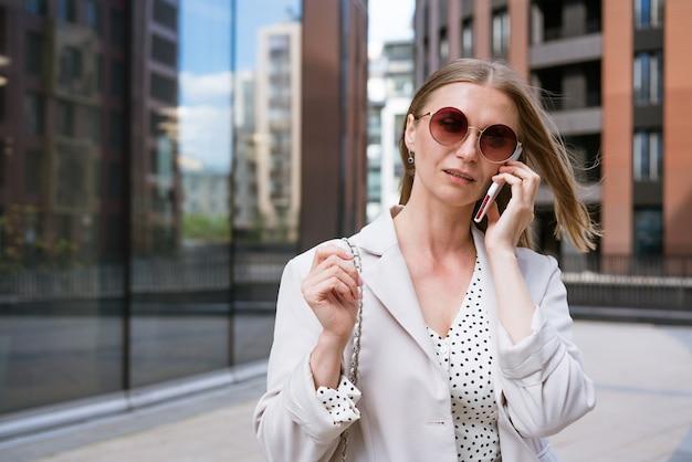 사무실 근처에 전화를 들고 있는 비즈니스 우먼 세련된 조명 사무실에서 웃고 있는 아름다운 소녀의 초상화...