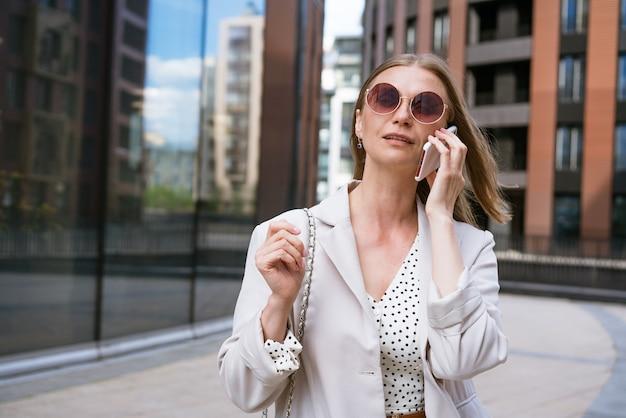 ファッショナブルな明るいオフィスで美しい笑顔の女の子のオフィスの肖像画の近くに電話を持つビジネス女性...