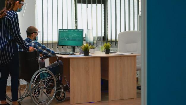 車椅子の障害者がデスクに着くのを助け、コロナウイルスのパンデミックの間に企業のオフィスで新しい通常の仕事をしている保護マスクを持ったビジネスウーマン。社会的距離を尊重するビジネスマン