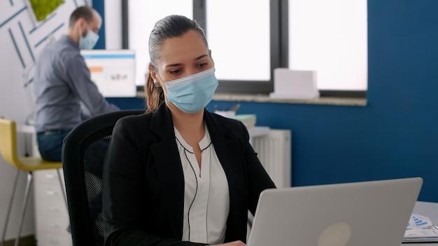会社のオフィスの机のテーブルに座って、ラップトップコンピューターのマーケティング統計を分析する保護フェイスマスクを持つビジネスウーマン。ウイルス病を回避するために社会的距離を保つ同僚